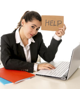 overworked business woman wearing a business suit working on her  laptop holding a help sign on a white background